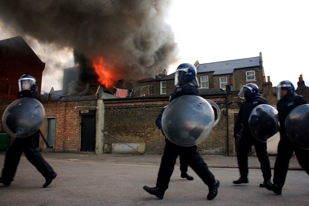 Police walk past blazing house